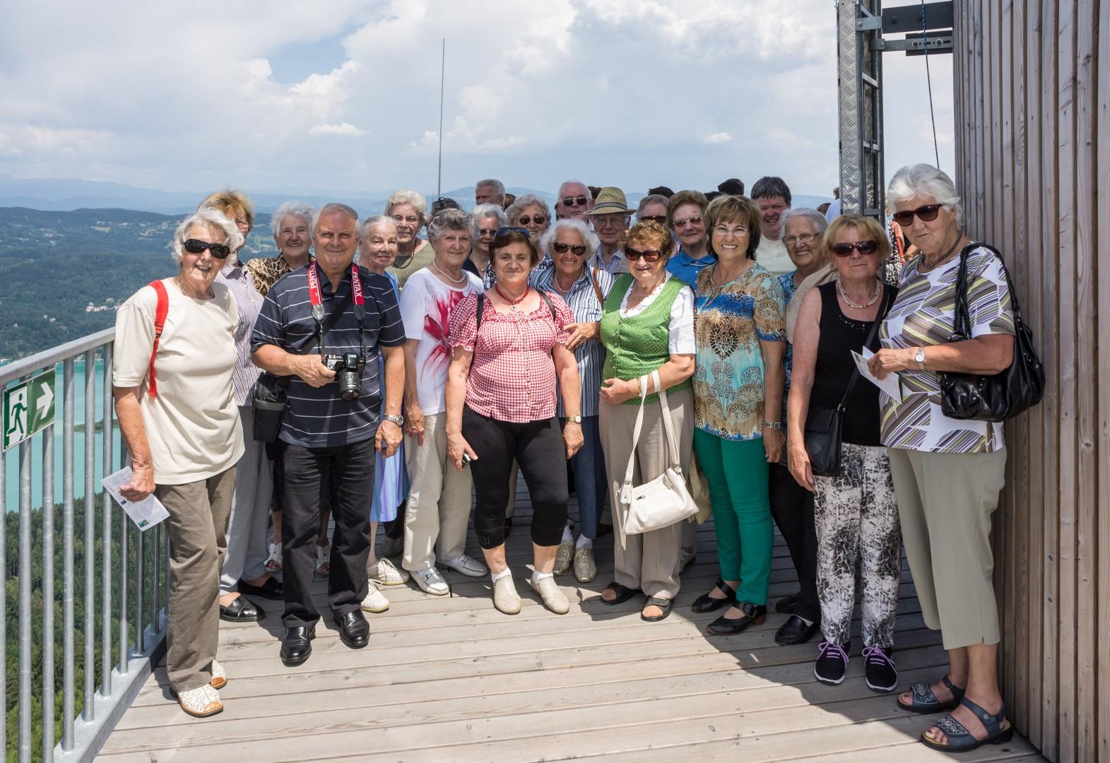 Das Seniorenteam gemeinsam mit Gruppenleiterin Frau Brigitte Kettner (links außen) beim Ausflug zum neuen Wahrzeichen Kärntens - Aussichtsturm Pyramidenkogel, am 12. Juni 2014, hier auf der obersten Aussichtsplattform neben dem Antennenmast in 70.56 m Turmhöhe und 919.06 m Seehöhe (© Herr Mag. Bernhard Wagner).