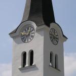 Nahansicht des St. Jakober Kirchturms in Blickrichtung Südwesten. Ost- und nordseitige Turmuhr sowie Schallfenster der Glockenstube (© Herr Mag. Bernhard Wagner).