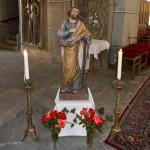 Eine andere, ebenfalls mit Blumen geschmückte Statue des Heiligen, flankiert von zwei Kerzenleuchtern mit brennenden Kerzen neben dem Volksaltar. Hier hält er nur die weiße Lilie (© Herr Mag. Bernhard Wagner).