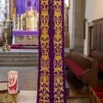 Verhüllung des Kreuzes beim Volksaltar der Markuskirche mittels einer violetten Stola. Ab dem auch Passionssonntag genannten 5. Fastensonntag ist es üblich, die Kreuze in den Kirchen zu verhüllen bis sie während der Karfreitagsliturgie wieder enthüllt werden (© Herr Mag. Bernhard Wagner).