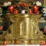 Tabernakel des Herz Jesu-Altars mit Blumenschmuck sowie zwei Kerzen und verschiedenen Lichtern in abendlicher Beleuchtung (© Herr Mag. Bernhard Wagner).