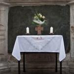 Altar am Hohen Platz bei der Mariensäule mit einem Bronzekreuz sowie Blumenschmuck und Kerzen. Auch hier gibt es in diesem Bild nicht zu sehende Birken (© Herr Mag. Bernhard Wagner).