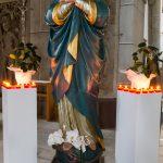 Madonnenstatue zum Fest Mariä Himmelfahrt am 15. August flankiert von zwei Säulen mit Blumenschmuck und Lichtern, zu Füßen der Madonna eine Orchidee (© Herr Mag. Bernhard Wagner).