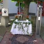 Altar am Offnerplatzl unter einem Kastanienbaum mit Blumenschmuck und Efeu, von Kunstwerken flankiert (© Herr Mag. Bernhard Wagner).