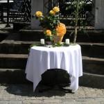 Altar am Hohen Platz bei der Mariensäule mit einem Bronzekreuz sowie Blumenschmuck und Kerzen. Im Hintergrund eine Birke (© Herr Mag. Bernhard Wagner).