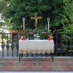 Altar am Markusplatz vor dem Portal der Markuskirche mit einem Messingkreuz, zwei Ministrantenleuchten sowie Blumenschmuck und Lichtern, flankiert von zwei Birken (© Herr Mag. Bernhard Wagner).