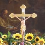Das Hochaltarkreuz umgeben von Sonnenblumen. Dahinter der Hl. Markus mit dem Löwen (© Herr Mag. Bernhard Wagner).