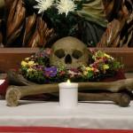 Totenkopf in einem Blumenkranz und Knochen flankiert von zwei Lichtern am Allerseelenaltar in abendlicher Beleuchtung (© Herr Mag. Bernhard Wagner).