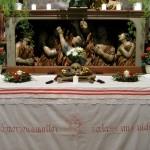 Unterer Teil des Allerseelenaltars in abendlicher Beleuchtung. Am Altartisch der Totenkopf mit den beiden Knochen, dem Blumenkranz und den Lichtern (© Herr Mag. Bernhard Wagner).