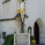 Krucifix und Kriegerdenkmal nahe den Eingängen zur Kirche (© Herr Mag. Bernhard Wagner).