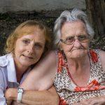 Die ehemalige Stadtpfarrmessnerin Frau Elfriede Koschier (rechts) und ihre Betreuerin vom Roten Kreuz Wolfsberg im Innenhof des Pfarrhofs (© Herr Mag. Bernhard Wagner).