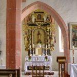 Der gotische Triumphbogen wird von zwei kleinen Seitenaltären flankiert, links auf einer Konsole eine Madonnenstatue, rechts Pestbild Schutzmantelmadonna (© Herr Mag. Bernhard Wagner).