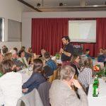 Herr Mokoru spricht zu den Anwesenden, im Hintergrund läuft ein Film über das Jugendzentrum vom ehemaligen Zivildiener Herrn Thomas Hafner, ... (Aufnahme: Herr Christoph Isopp; © Katholische Jugend Lavanttal)