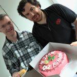 Herr Mag. Bernhard Wagner (links) und Herr Mokoru präsentieren die Avalon-Torte anlässlich des 15. Geburtstags (© Katholische Jugend Lavanttal).