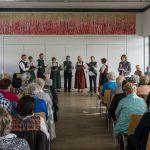 Frau Kölbl-Perner an die Gäste gewandt und der Singkreis bereitet sich derweil auf das nächste Lied vor (© Herr Mag. Bernhard Wagner).