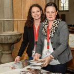 Zwei junge Damen empfangen die Gäste beim Portal der Markuskirche und teilen die Programmhefte zum Fest aus (© Herr Gerhard Pulsinger).