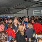 Zahlreiche Menschen haben sich zu einem gemütlichen Beisammensein im Zelt vor der Markuskirche versammelt. Es gibt Leberkässemmel, Reindling sowie Kaffee und verschiedene Getränke (© Herr Gerhard Pulsinger).