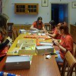 """In den Räumlichkeiten des Pfarrhofs versieht eine Mädchengruppe Schuhkartons mit Geschenkpapier und befüllt sie sodann u.a. mit Süßigkeiten und Spielzeug für """"Weihnachten im Schuhkarton"""" (© Katholische Jugend Lavanttal)."""