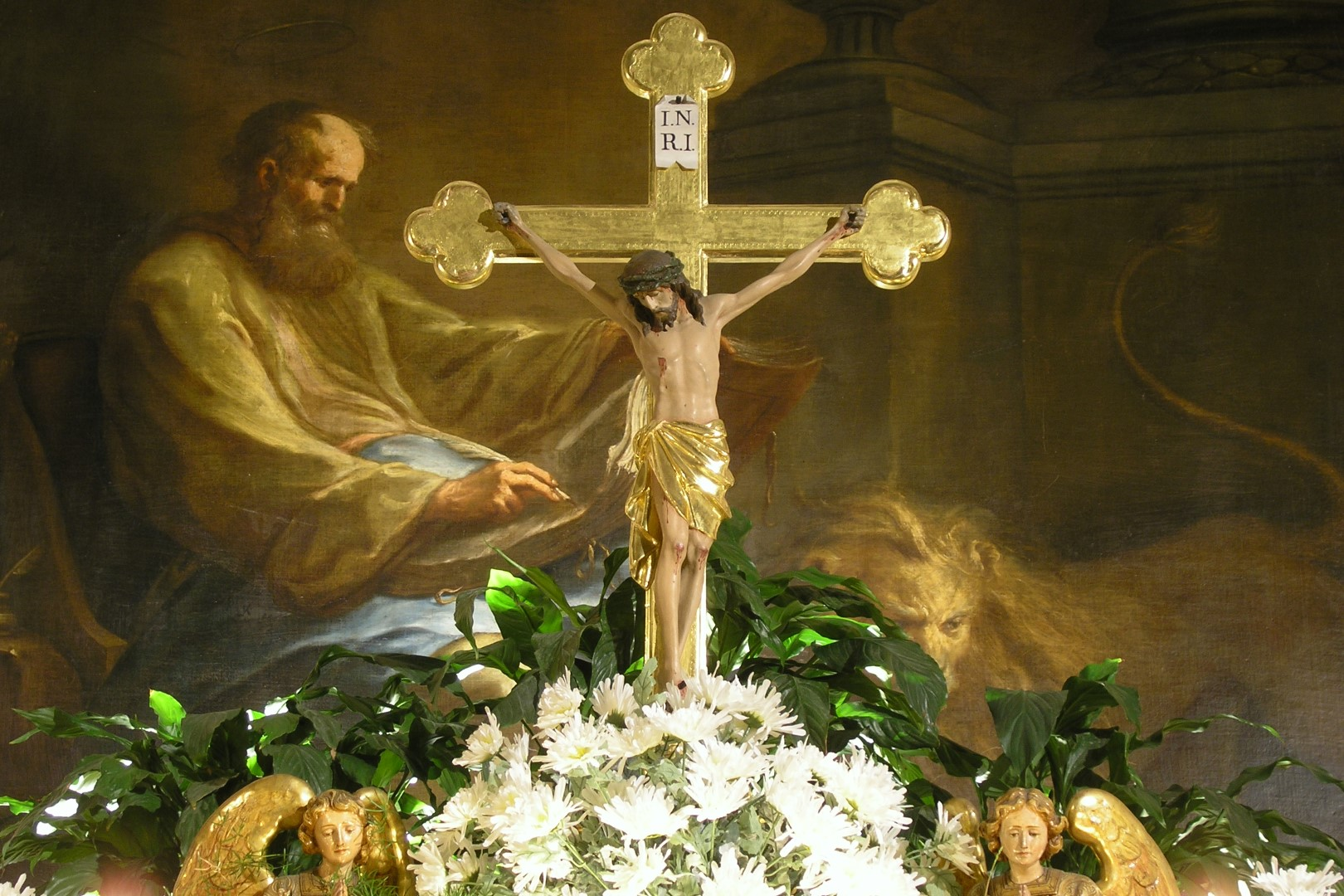 Hochaltarkreuz in der Markuskirche Wolfsberg, im Hintergrund das Altarbild mit dem Hl. Markus (© Mag. Bernhard Wagner).