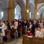 Blick in das Hauptschiff der Kirche zu den Erstkommunionkindern mit den brennenden Kerzen (© Herr Mag. Bernhard Wagner).