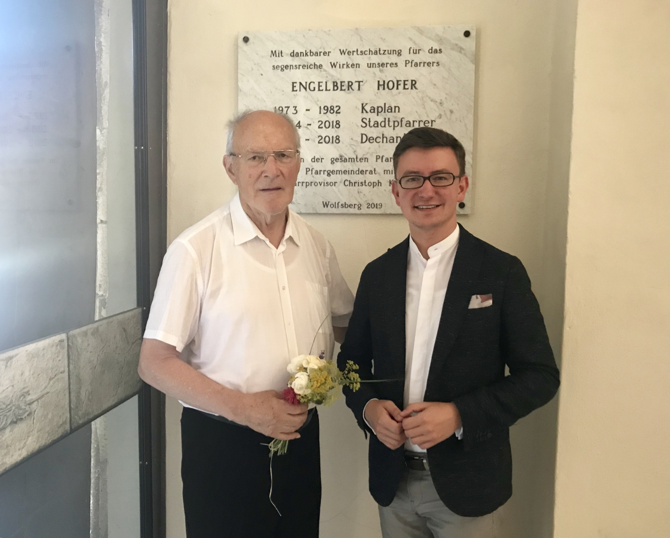 Pfarrer Emeritus Mag. Engelbert Hofer (links) zusammen mit Pfarrprovisor Mag. Dr. Christoph Kranicki vor der Danktafel neben dem Haupteingang der Markuskirche (© Pfarre Wolfsberg).