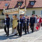 Der Provisor und das Allerheiligste unter dem von Männern der Feuerwehr getragenen Himmel auf der Radlstegbrücke am Weg zum Feuerwehr-Rüsthaus (© Herr Mag. Bernhard Wagner).